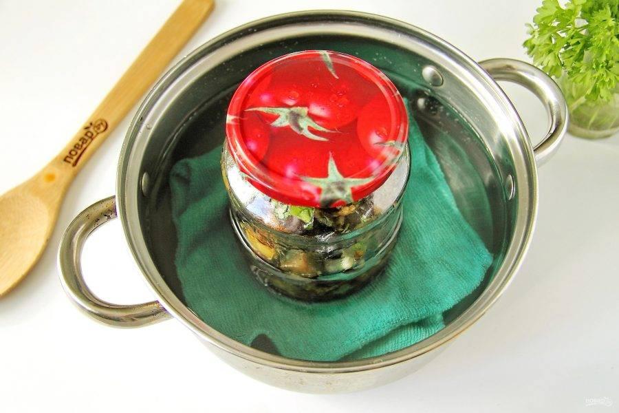 Прикройте банки стерильными крышками и поставьте в кастрюлю. Налейте в кастрюлю воду и стерилизуйте банки 25 минут. На дно обязательно положите небольшое полотенце, чтобы банка не лопнула. Затем банки закатайте, переверните вверх дном, укутайте и оставьте до остывания. Храните закуску в прохладном месте.