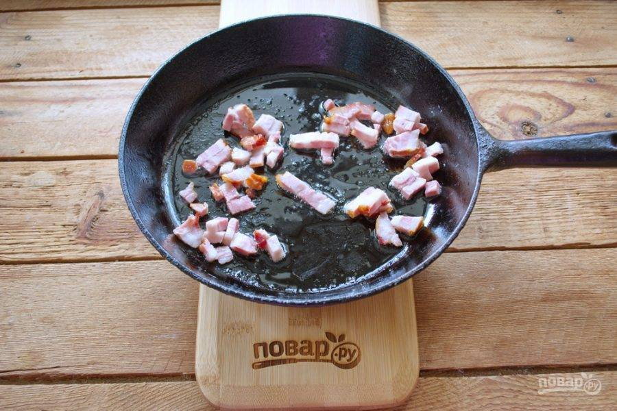 Небольшое количество бекона обжарьте на растительном масле. Когда бекон вытопится (3-5 минут), добавьте еще немного растительного масла и вылейте в сковороду подготовленную омлетную массу.
