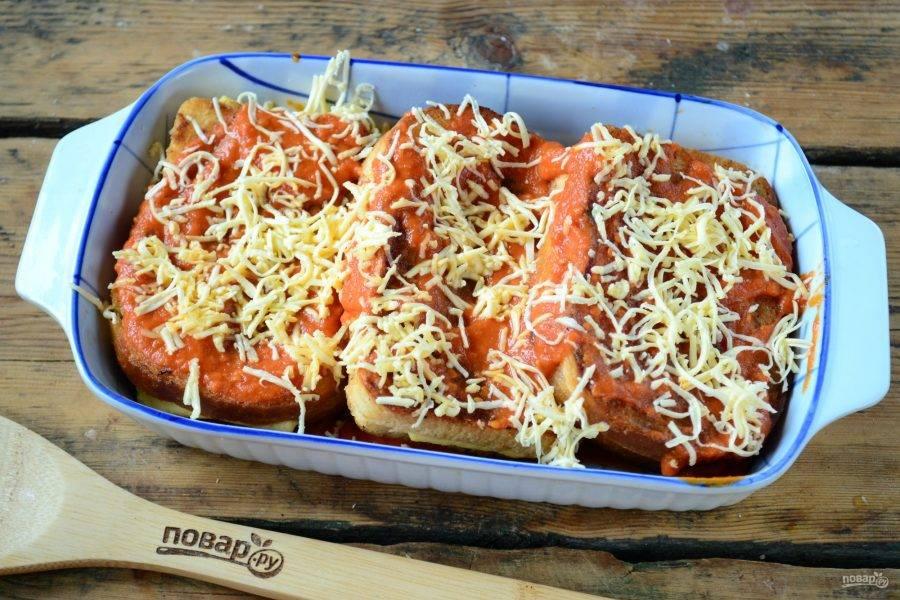 Сверху еще смажьте томатным соусом. Оставшийся сыр натрите на мелкой терке, присыпьте им бутерброды сверху.