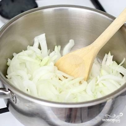2. В кастрюлю с маслом выложите нарезанный лук. При помощи лопаточки распределите его равномерно по дну.