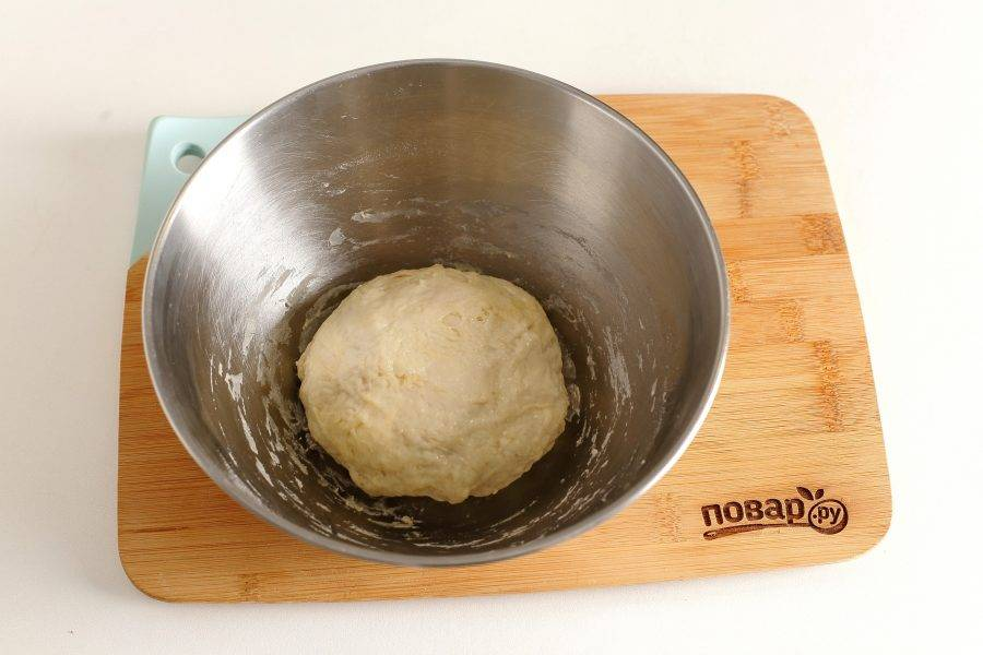 Замесите мягкое, чуть липкое тесто. Соберите его в шар, смажьте маслом, накройте миску пищевой пленкой и оставьте в теплом месте примерно на час.