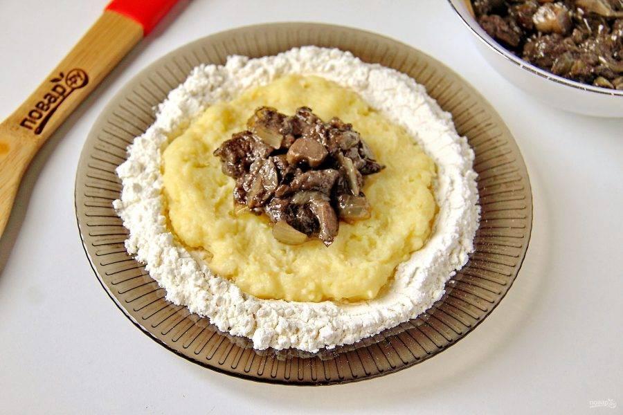 Насыпьте на тарелку ровным слоем муку и положите на нее немного картофельной массы. Придайте картофелю форму лепешки и выложите по центру начинку.