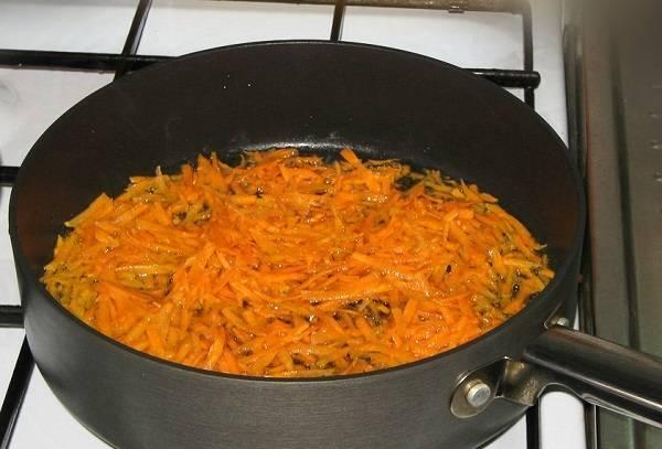 1. Первым делом лучше заняться подготовкой всех ингредиентов, чтобы это не замедляло процесс приготовления. Морковь нужно очистить и натереть на терке. Капусту нашинковать, а перец очистить и измельчить. На сковороду налить немного растительного масла и выложить туда морковь.