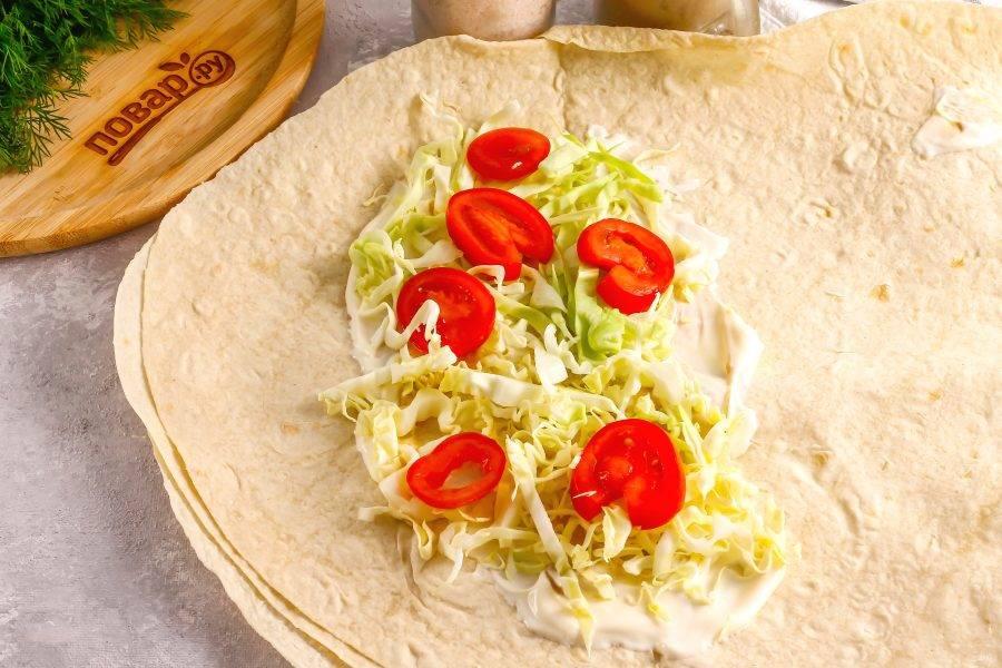 Расстелите лаваш на рабочей поверхности, смажьте 1 ст.л. майонеза и 1 ч.л. горчицы. Выложите нарезку капусты и помидоров.