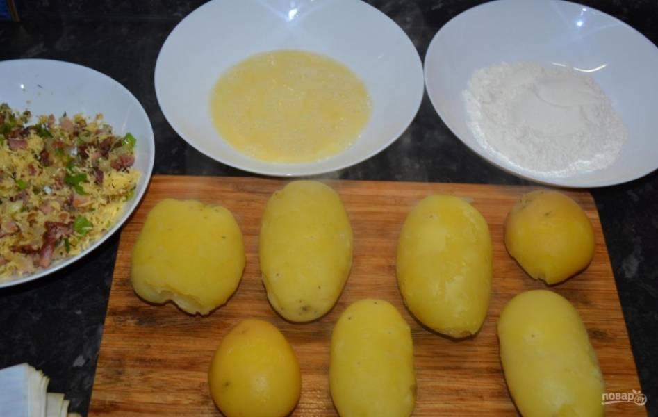 6.Картошку мою и отвариваю, выбираю примерно одинакового размера. Достаю картошку и немного остужаю, затем снимаю кожуру. В одну миску вбиваю куриные яйца, перемешиваю их, в другую кладу муку.