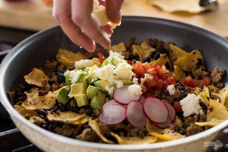 5. Поместите в сковороду с фаршем измельченный помидор, редис и авокадо. Присыпьте тертым сыром.