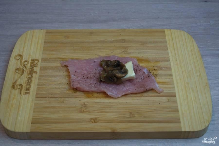 Мясо отбейте молоточком. Посолите, поперчите. На край пласта мяса уложите кусочек сливочного масла. Добавьте немного обжаренных грибов.