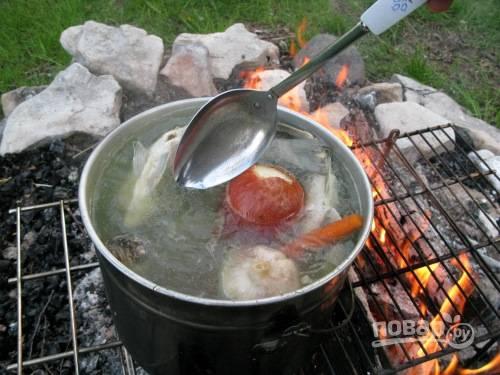 В котелок положите неочищенный репчатый лук, головку чеснока, целую морковь, соль и перец. Пусть бульон кипит не менее 40 минут.