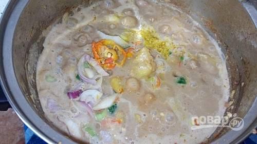 5.Добавьте в кастрюлю чили, лук, соль, чеснок, куриные кубики.