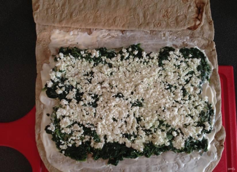 4.Брынзу достаю из упаковки и разминаю руками, затем выкладываю поверх шпината и немного придавливаю вилкой.