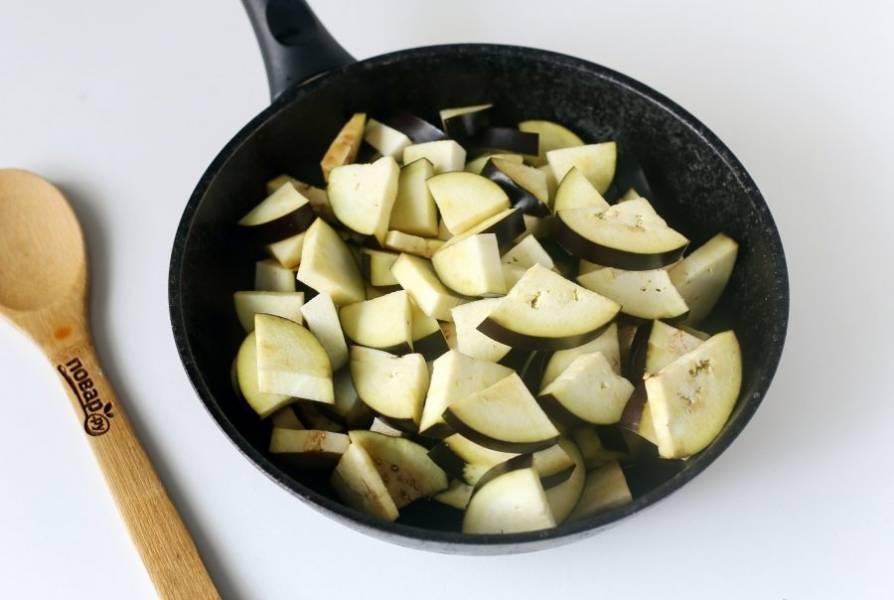 В сковороде разогрейте масло и выложите нарезанные крупными кусочками баклажаны.