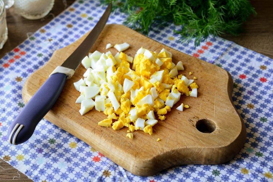Куриные яйца сварите вкрутую и почистите. Нарежьте кубиками для салата.