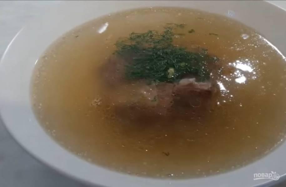 5. Посолите бульон и томите мясо, пока оно не начнет легко отделяться от кости. Разлейте бульон по тарелкам и украсьте зеленью. Приятного аппетита!