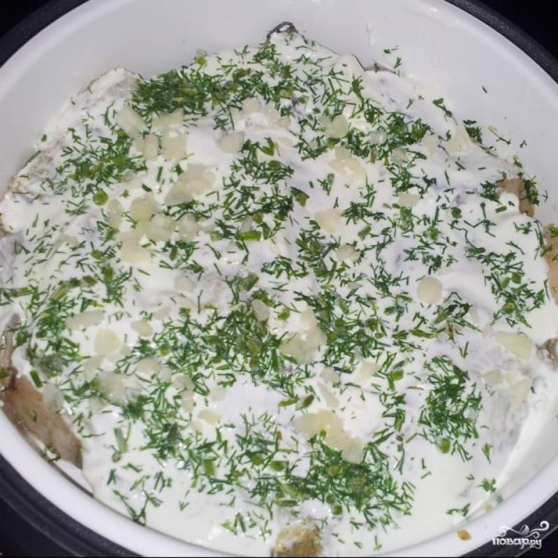 Рыбу смешать со специями, выложить в контейнер для варки на пару. Смазать сметаной, посыпать укропом и мелко нарезанным чесноком.