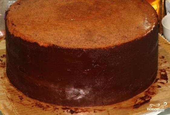 Сделайте ганаш. Оставшийся шоколад растопите на водяной бане, затем сразу же влейте сливки и перемешайте. Остудите массу. Обмажьте ею полностью весь торт.