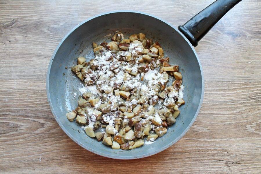 Обжаренные грибы посыпьте мукой, перемешайте и обжарьте еще 2 минуты.