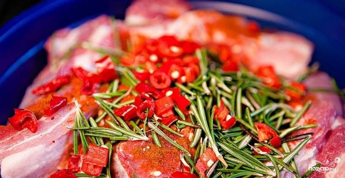 2.Вымойте перец чили и розмарин. Мясо посолите со всех сторон и сложите в миску. Обильно посыпьте паприкой и совсем немного острым перцем. Порежьте перец чили кусочками, чтобы убрать излишнюю остроту, удалите семена и добавьте к ребрам. С розмарина оторвите листья и тоже отправьте в миску.