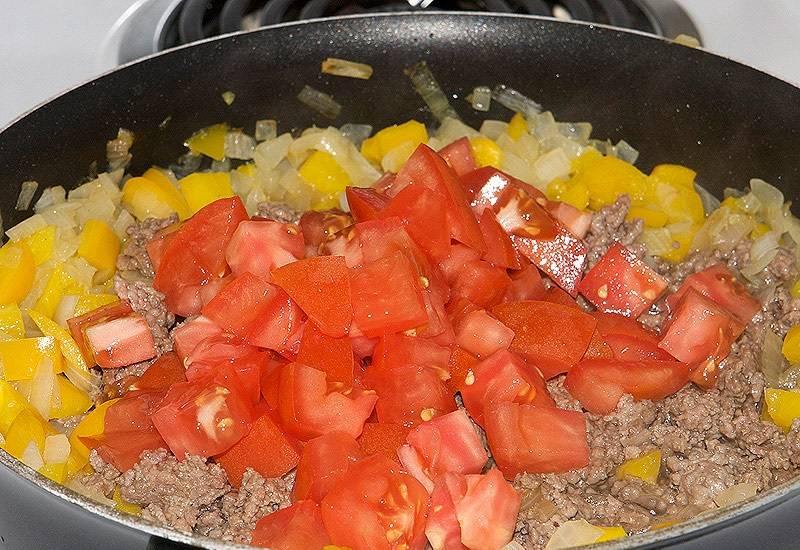 5. Вымыть, обсушить и измельчить помидор. В зимнее время в этот простой рецепт жареных баклажанов под мясом можно использовать томатный соус.