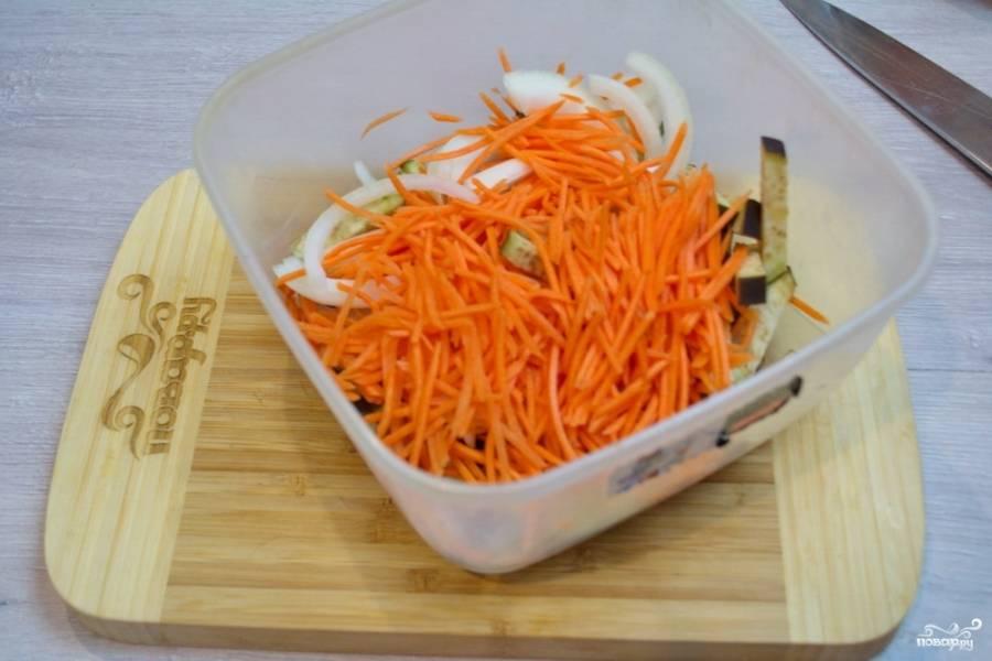 Натрите морковь или нарежьте тонкой соломкой. Лучше всего использовать терку для корейской морковки. Добавьте измельченную морковь к баклажанам. Нарежьте репчатый лук полукольцами и добавьте его к другим овощам.