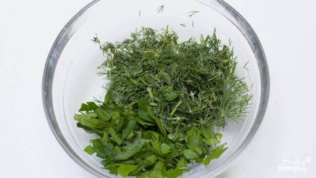 4. Пока уха варится, вымойте, обсушите и измельчите зелень.