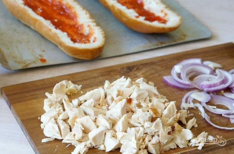 2.Смажьте соусом каждую половинку. Нарежьте небольшими кубиками курицу, красный лук - тонкими полукольцами.