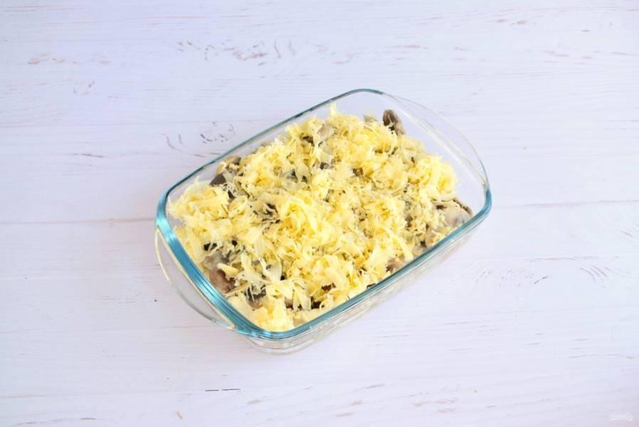 Сверху посыпьте тертым сыром. Поставьте запекаться в разогретую до 180-200 °С духовку на 15 минут до расплавления сыра.