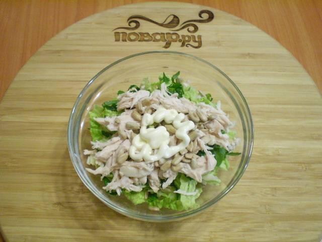Соедините капусту, зелень, куриное филе, соль, специи, майонез и жареные очищенные семечки.