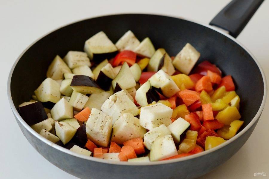 Добавьте морковь, перец и баклажан. Обжаривайте овощи на среднем огне 10 минут.