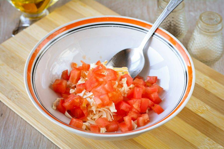 Нарежьте кубиками помидоры и добавьте к сыру.