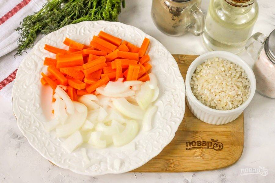 Морковь и репчатый лук очистите от кожуры, промойте в воде и нарежьте морковь брусочками, а лук — полукольцами.