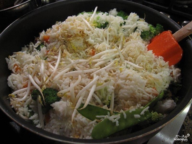 Затем добавляем в сковороду сваренный до полуготовности рис, ростки, соль и растительное масло. Сюда же добавляем 2 столовые ложки соуса, который мы готовили для мяса. Жарим на быстром огне около 5 минут, активно помешивая.