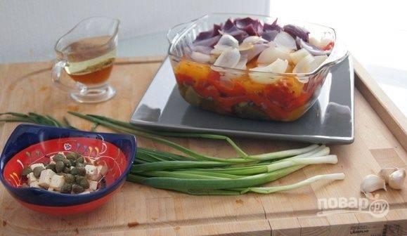 В отдельной емкости приготовьте заправку для салата. Смешайте в ней уксус, масло, соль, перец, мелко нарезанный лук, чеснок, фету и каперсы.