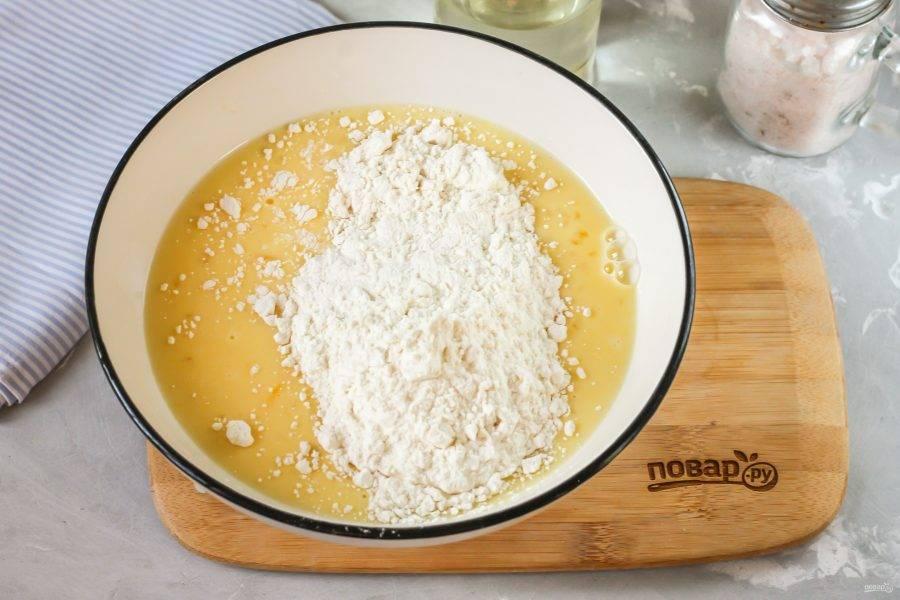 """Вбейте куриные яйца в глубокую емкость. Взбейте их с сахаром и солью, влейте молоко любой жирности и аккуратно все перемешайте. Всыпьте пшеничную муку и взбейте все содержимое так, чтобы не образовались комочки. Влейте растительное масло, вмешайте его и дайте тесту """"отдохнуть"""" 15 минут."""