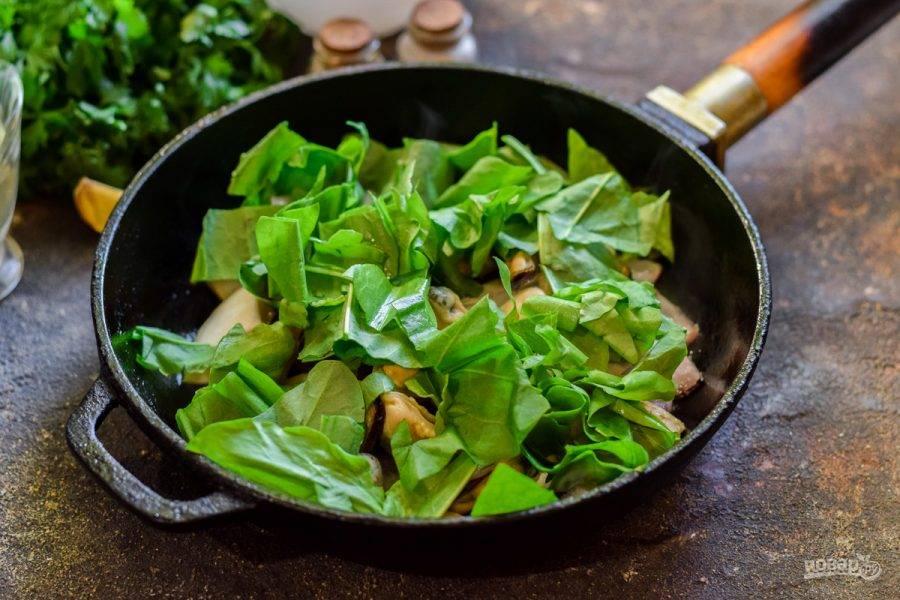 Добавьте в сковороду шпинат, соль, перец, сухой чеснок. Перемешайте и прогрейте минуту, чтобы шпинат уменьшился в объеме.