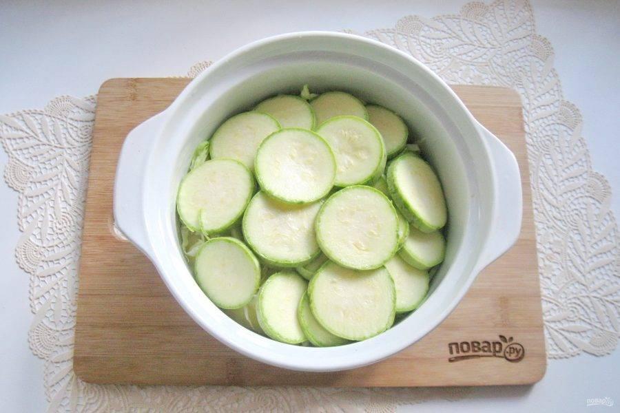 Кабачки помойте. Молодые чистить не нужно. Нарежьте кружками толщиной 1 см. Выложите в кастрюлю. Еще немного посолите.