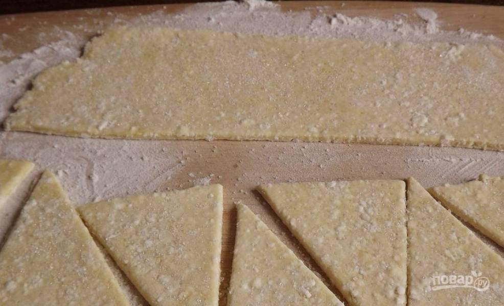 Когда тесто охладится, освободите его от пленки, выложите на рабочую поверхность и раскатайте в пласт. Разрежьте тесто на прямоугольники, посыпьте их сахаром, выложите по ложке повидла и сверните тесто в рогалики.
