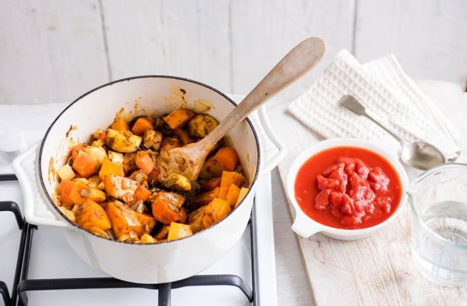 4. Добавьте в кастрюлю измельченные помидоры и воду. Тушите овощи в течение 25 минут на среднем огне.