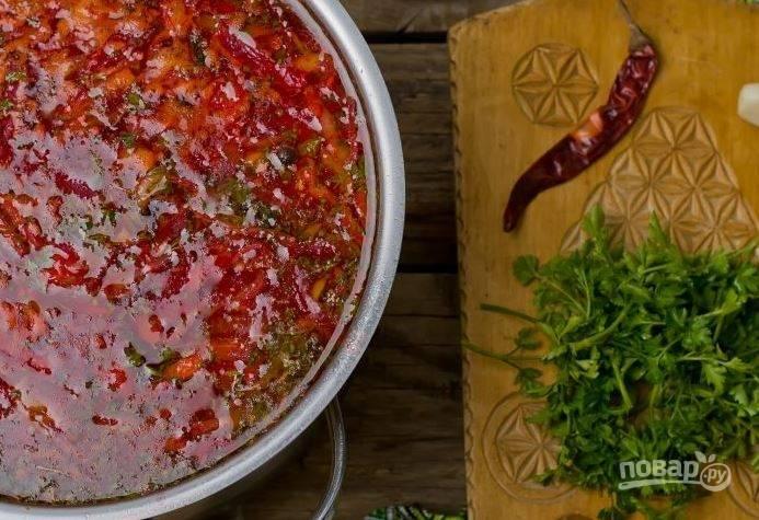 Добавьте в борщ томатную пасту и капусту. Вымойте сладкий перец, нарежьте его полосочками и добавьте в кастрюлю. Когда борщ закипит, бросьте в него измельченный чеснок, перец и рубленую зелень. Посолите по вкусу, дайте закипеть и выключите огонь. Затем дайте борщу настояться.