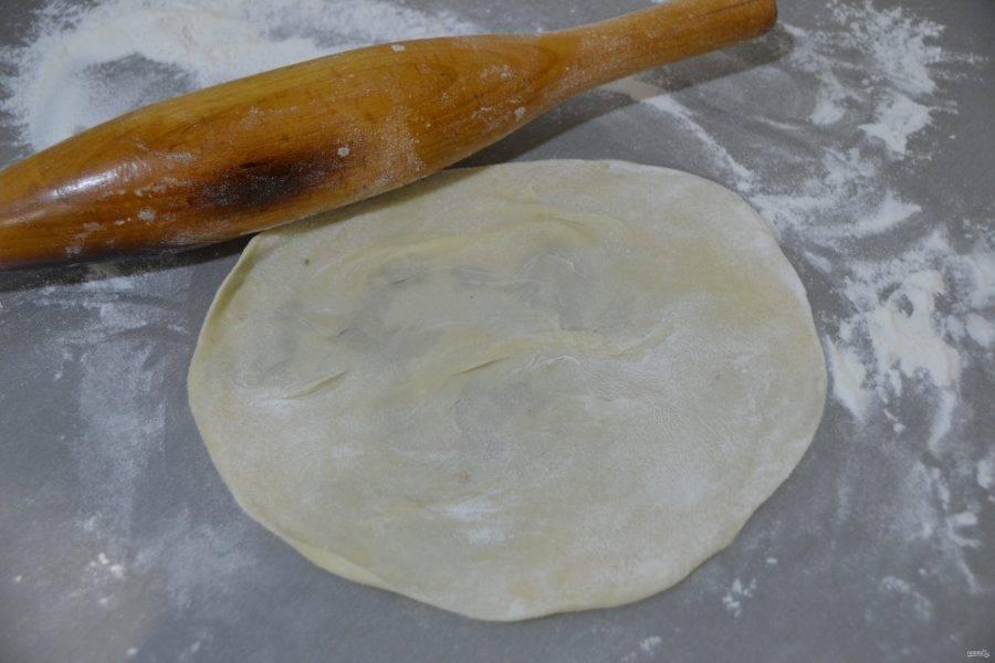 Присыпьте рабочий стол мукой, раскатайте тесто в пласт диаметром примерно 18-20 см.