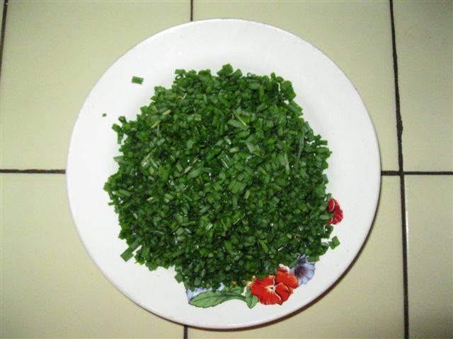 2. Тем временем можно вымыть и измельчить зелень. В этом рецепте пирожков используется только лук, однако можно взять любую зелень по вкусу.
