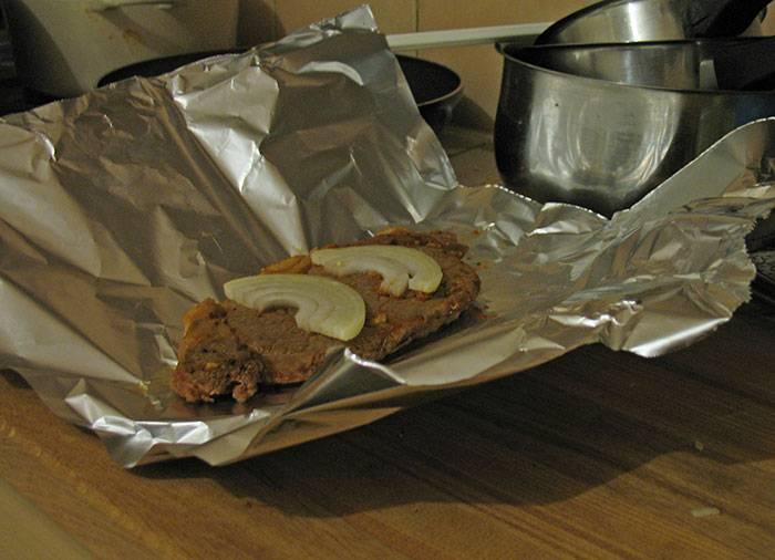 Обжарили мясо на разогретой сковороде в масле. Добавили немного воды, горчицу и соус. Затем выложили в фольгу, сверху положили пару колец лука.