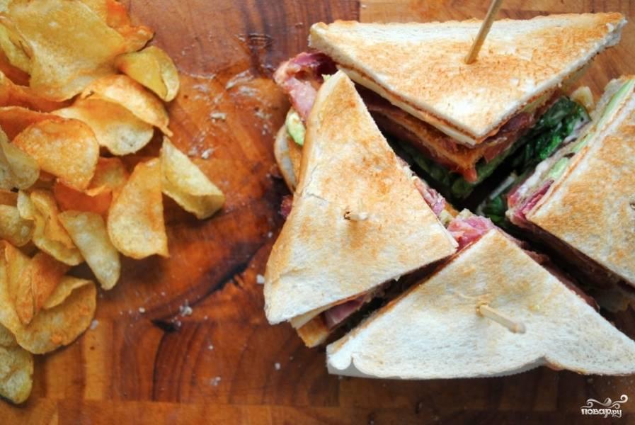 Воткнуть зубочистки и острым ножом разрезать сэндвич на 4 части.