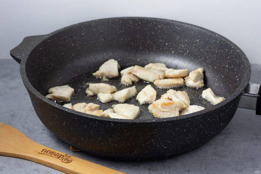 На растительном масле обжарьте кусочки куриного филе до готовности. Немного посолите.  Уберите курицу со сковороды.