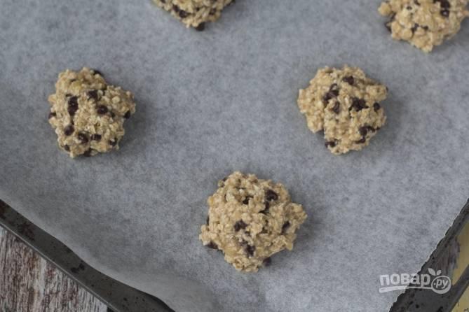 Затем вмешайте шоколадные капли. Противень устелите пергаментом, сформируйте небольшие печеньки и выложите на противень.