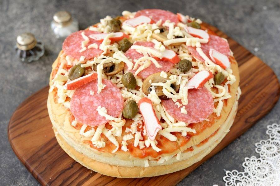 Последнюю половину коржа для пиццы снова смазываете соусом и посыпаете моцареллой, выкладываете оставшуюся салями, ломтики обжаренных грибов, кусочки крабовых палочек и посыпаете все каперсами или маслинами. Отправьте заготовку в предварительно разогретую до 180 градусов духовку на 20 минут без конвекции, чтобы сыр расплавился, а все ингредиенты хорошо прогрелись.