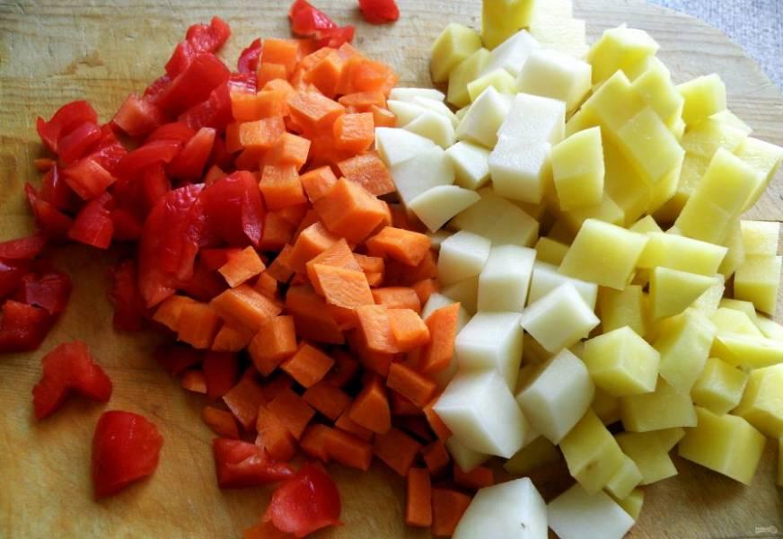 Овощи очистите и нарежьте мелкими кубиками. Опустите в суп и варите почти до готовности.