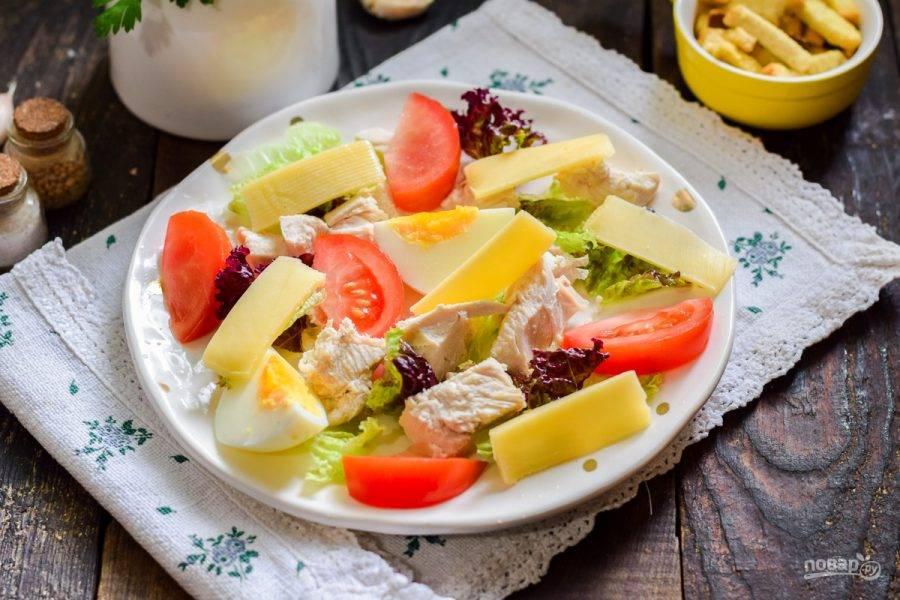 Далее выложите в салат дольки помидоров и нарезанный сыр.