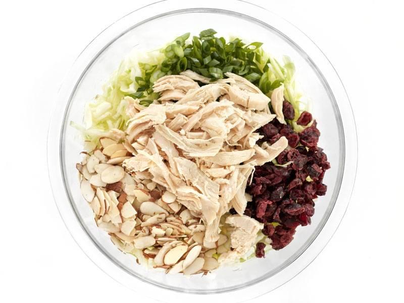 3.Капусту промываю и вытираю салфетками, перекладываю в миску. Куриное филе разделяю на волокна и добавляю в салатник, зеленый лук мою и нарезаю мелко, миндаль измельчаю, выкладываю все ингредиенты, добавляю сушеную клюкву.