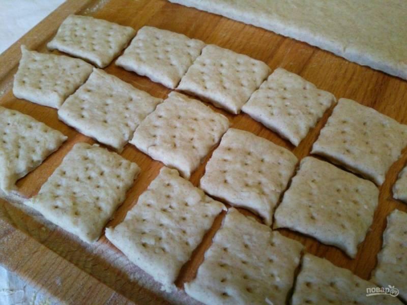 Обомните тесто руками, раскатайте его в пласт толщиной 5-6 мм, а затем разрежьте на небольшие прямоугольные кусочки и проколите их вилкой в нескольких местах.