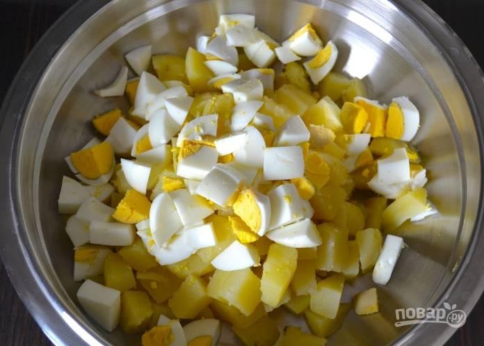 1.Отвариваю картофель и яйца, остужаю, чищу и нарезаю все небольшими кубиками, отправляю в миску и перемешиваю.